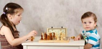 Ernste Kinder, die Schach spielen Stockfotos