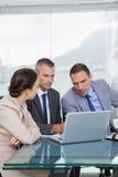 Ernste Kollegen, die zusammen an ihrem Laptop arbeiten Lizenzfreies Stockfoto