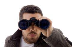 Ernste männliche Betrachtung durch Binokel lizenzfreies stockbild