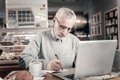 Ernste männliche Person, die Ideen auf Papier schreibt stockfotografie