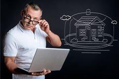 Ernste Mannplanung, die das Haus kauft lizenzfreie stockfotos