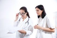 Ernste medizinische Arbeitskräfte, die Dokumentation betrachten Lizenzfreie Stockfotografie