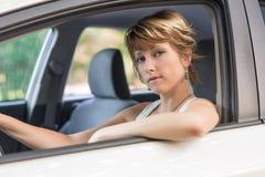 Ernste recht blonde junge Frau, die Auto fährt Lizenzfreies Stockbild