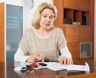 Ernste reife Frau, die das Familienbudget berechnet Stockbild