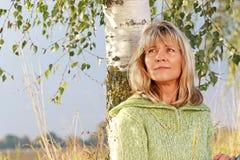 Ernste reife Frau, die in der Natur sich entspannt Lizenzfreie Stockfotografie