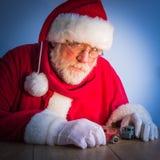 Ernste Santa Claus spielt mit Weinlesespielwarenautos zu Hause Stockfotografie
