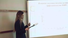 Ernste schöne Geschäftsfrau sagt, dass Bericht und das Darstellen auf einen Projektor im Vorlesungssal schiebt stock footage