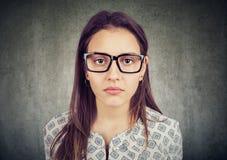 Ernste schauende junge Frau in den Gläsern stockfoto