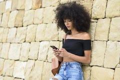 Ernste schwarze Frau, die draußen ihr intelligentes Telefon betrachtet Stockbild