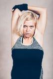 Ernste sportliche Eignungsfrau, die Arme ausdehnt Lizenzfreie Stockfotografie