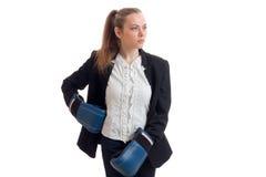 Ernste starke blonde Geschäftsfrau in der Uniform und in Boxhandschuhen, die weg schauen Stockfotos