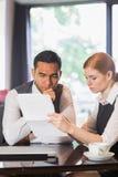 Ernste Teilhaber, die in einem Café zusammenarbeiten Stockbild