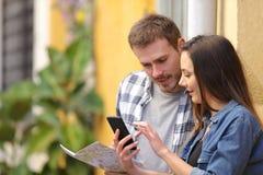 Ernste Touristen, die im Urlaub Telefon überprüfen stockfotos