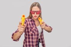 Ernste und starke junge Frau schaut durch rote Gläser Sie hält Wasserpistolen in den Händen Modellhaltungen auf Kamera lizenzfreie stockbilder