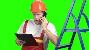 Ernste Vorarbeiter, die am Handy sprechen stock video