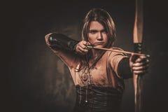 Ernste Wikinger-Frau mit Pfeil und Bogen in einem traditionellen Krieger kleidet und wirft auf einem dunklen Hintergrund auf lizenzfreie stockfotos