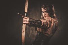 Ernste Wikinger-Frau mit Pfeil und Bogen in einem traditionellen Krieger kleidet und wirft auf einem dunklen Hintergrund auf lizenzfreie stockfotografie