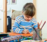 Ernste Zeichnung mit drei Jährigen auf Papier Stockfotos