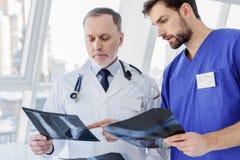 Ernste zwei Ärzte für Allgemeinmedizin, die Röntgenstrahlbild besprechen Lizenzfreie Stockfotos