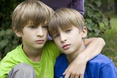Ernste Zwillinge, die im Park umarmen Lizenzfreie Stockfotos