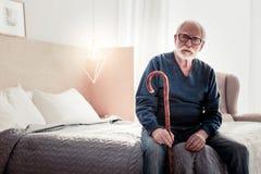 Ernster älterer Mann, der einen Spazierstock hält lizenzfreies stockfoto
