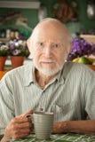 Ernster älterer Mann mit Becher Stockfotografie