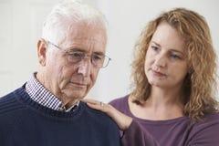 Ernster älterer Mann mit erwachsener Tochter zu Hause stockfotografie