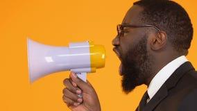 Ernster afroer-amerikanisch Mann in der Klage schreiend im Megaphon, Markttendenzen ankündigend stock video footage