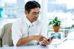 Ernster asiatischer Geschäftsmann unter Verwendung der Tablette Stockfotos