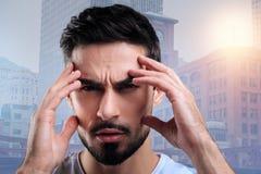 Ernster aufmerksamer die Stirn runzelnder Student bei der Konzentration an der Prüfung lizenzfreies stockfoto