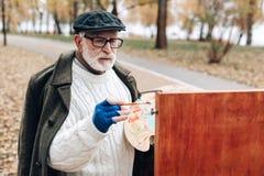 Ernster bärtiger reifer Mann, der an seinem Projekt arbeitet lizenzfreies stockbild