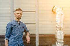 Ernster b?rtiger junger Mann im Denimhemd steht nahe der Wand des Industriegeb?udes nahe Leiter und betrachtet direkt  lizenzfreies stockbild