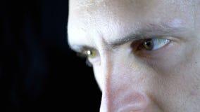 Ernster Blick eines jungen Mannes, der Arbeiten auf einen schwarzen Hintergrund konzentrierte Langsame Bewegung stock video footage