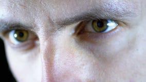 Ernster Blick eines jungen Mannes, der Arbeiten auf einen schwarzen Hintergrund konzentrierte Langsame Bewegung stock footage