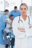 Ernster blonder Doktor, der mit Kollegen im Hintergrund aufwirft Stockfotografie