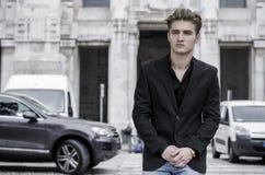 Ernster blonder junger Mann in den Jeans und in Jacke, draußen sitzend Lizenzfreies Stockfoto
