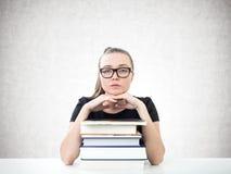 Ernster blonder Student, Bücher, konkret Lizenzfreie Stockfotos