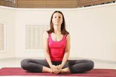 Ernster Brunette, der Yoga ausübt lizenzfreie stockfotografie
