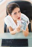 Ernster Buchhalter, der einen Taschenrechner betrachtet Kamera hält Lizenzfreie Stockfotografie