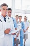 Ernster Doktor, der Klemmbrett und Stellung vor seinem ich hält Stockfoto
