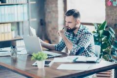 Ernster, durchdachter, bärtiger Kerl, der am Desktop in Arbeit plac sitzt Lizenzfreies Stockfoto