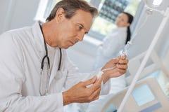 Ernster durchdachter Doktor, der ein Rohr IV hält stockbilder