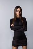 Ernster erwachsener Brunette im schwarzen Kleid auf grauem Hintergrund lizenzfreie stockfotografie