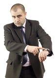 Ernster erwachsener Geschäftsmann, der auf seine Uhr zeigt Stockfoto