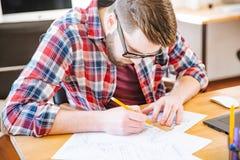 Ernster fleißiger Student, der am Schreibtisch und am zeichnenden Plan sitzt Stockfotografie