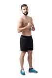 Ernster fokussierter geeigneter hemdloser Athlet, der die Wasserflasche betrachtet Kamera hält Stockfotos