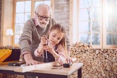 Ernster gealterter Mann, welche seiner Enkelin hilft Stockfoto