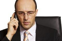 Ernster Geschäftsmann auf Handy Stockfotos