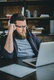 Ernster Geschäftsmann in den Kopfhörern, die zu Hause Büro bearbeiten Stockfotografie