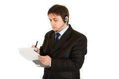 Ernster Geschäftsmann, der Anmerkungen im Dokument bildet Stockbilder